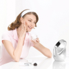 Sat at a desk using the mirror to help apply moisturiser