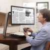 """A woman sitting at a table reading a magazine with the ClearView C 24"""""""" HD Desktop Video Magnifier"""