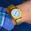 Gold talking watch being worn on a wrist.