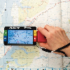 Ruby handheld video magnifier being used to read a road atlas
