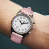 Small radio controlled talking watch with silver case, white face and pink strap on a wrist