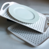 Tray being held at an angle with a plate secured by the anti-slip material
