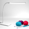 The lamp switched on with balls of wool and knitting needles under the light