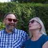 A woman and man sitting in the garden wearing Elipse eyeshields with grey filters.