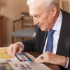 gentleman with shirt and tie reading a newspaper with the Compact+ HD portable video magnifier