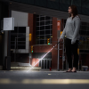 Side view of a woman using the cane light on a cane in a street