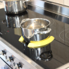 Two yellow Pan Pickles holding an empty pot in place on an induction hob