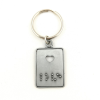 Keyring at a side angle with a punched heart-shaped hole and the word 'love' brailled underneath