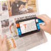 Hands holding theCompact+ HD portable video magnifier over a newspaper