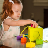 A second child playing with the Oombee Cube shape sorter