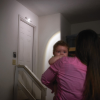 A person and a child approaching a door with the lamp above it