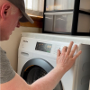 Man adjusting the dial on the washing machine