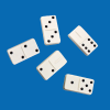 Close-up of a few white dominoes with raised black dots on a blue background