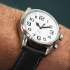 Angled view of Peregrine talking watch with black strap and white face on a wrist