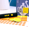 RNIB PenFriend 2 with sheets of recording labels next to a box of tea bags with a yellow label