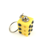 Braille cube keyring showing two sides, one with the letter L and one with a full six-dot cell