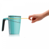 A person trying to tip over a blue anti-spill suction mug using a rubber band