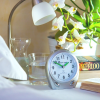 The clock sits upon a bedside table