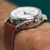 Large radio-controlled watch with silver case, white face and brown strap on a wrist showing buttons