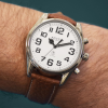 Large radio-controlled watch with silver case, white face and brown strap on a wrist