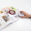 Magnifier opened to show magnifying lens on a magazine