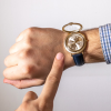 Watch on wrist with lid open and a finger pointing at dial
