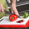 A person using the non-slip mat to hold a chopping board while chopping peppers